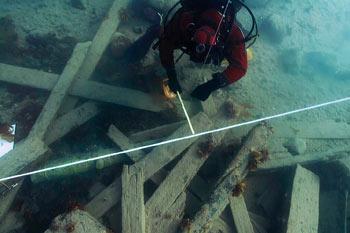 Un Archéologue de Parcs Canada mesurant la position d'un canon en utilisant une ligne de référence sur lesite HMS Erebus dans le « champ de débris » près de la coque de l'épave.